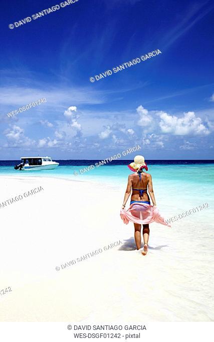 Maldives, woman walking on sand beach