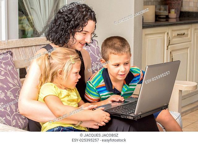 A mother and her two children, a girl and a boy, are looking with much interest at something on a silver laptop while sitting outside on the patio