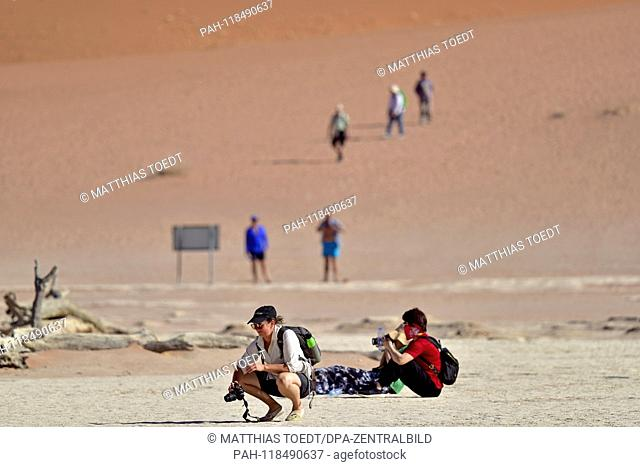Asian tourists in Dead Vlei, taken on 01.03.2019. The Dead Vlei is a dry, surrounded by tall dune clay pan with numerous dead acacia trees in the Namib Naukluft...