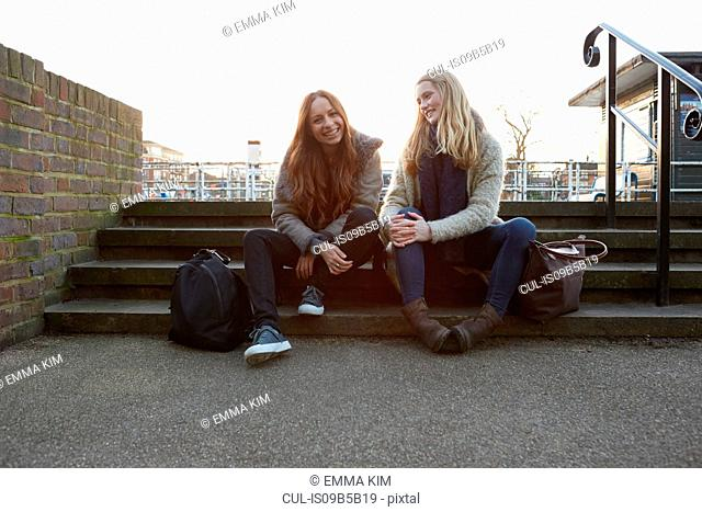 Two female friends outdoors, sitting on steps, smiling