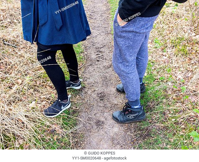 Regte Heide, Riel, Netherlands. Leggs and feet of a man and a woman strolling a nature reserve forest