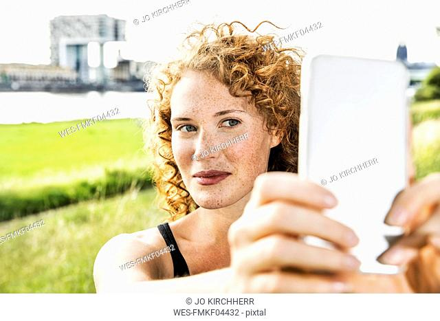 Germany, Cologne, portrait of freckled young woman taking selfie with cell phone