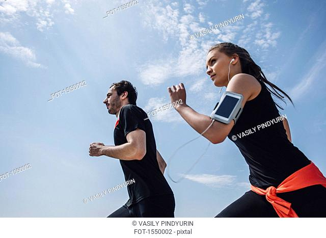 Low angle view of young man and woman jogging against sky