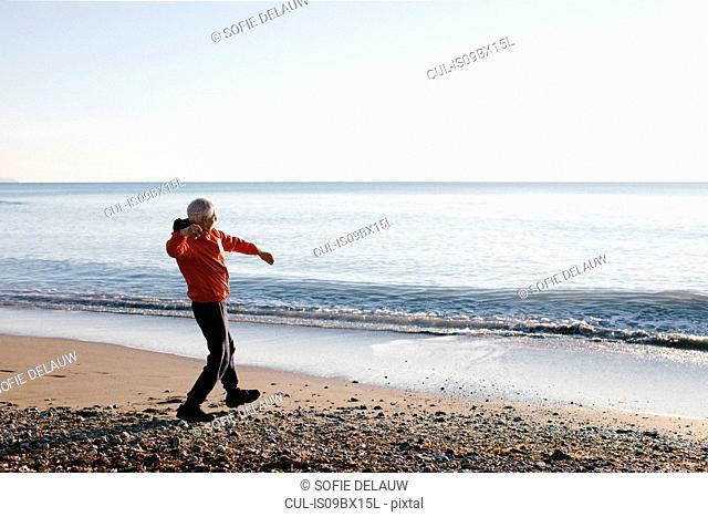 Senior man throwing pebbles into sea, Livorno, Italy