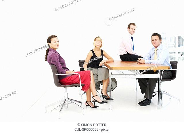 Seated business people look to camera