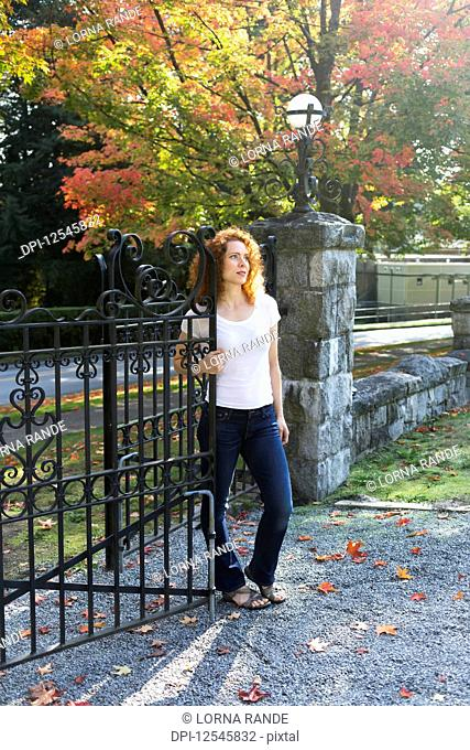 Portrait of a woman with red, curly hair standing at an open gate in autumn; Burnaby, British Columbia, Canada