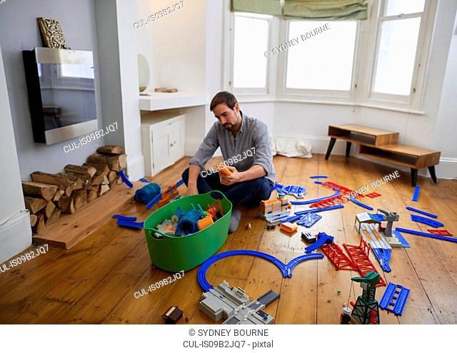 Mid adult man contemplating toys scattered in living room