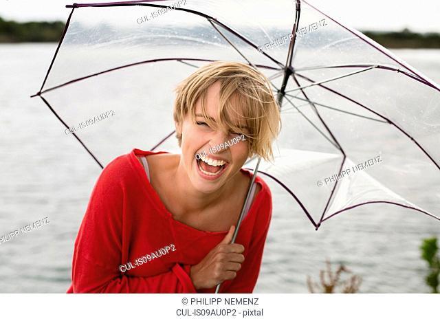 Happy young woman holding transparent umbrella at lake