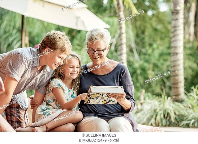 Older Caucasian woman and grandchildren looking at photo album