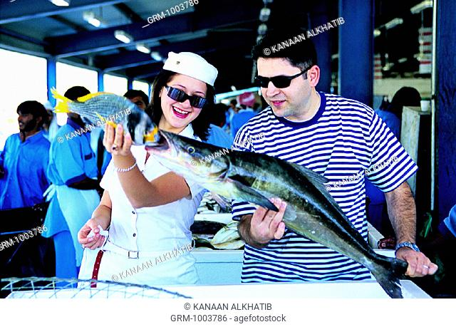 Western tourists on the fish market in Dubai, UAE