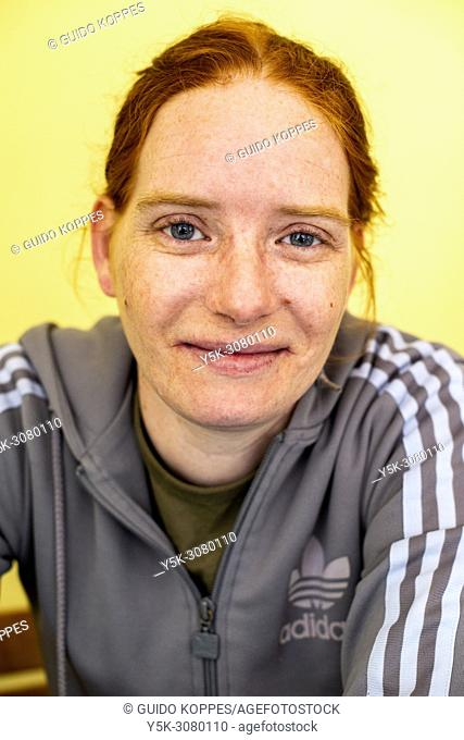 Tilburg, Netherlands. Studio-portrait of a cigarette smoking, redhaired woman wearing a branded shirt against a yellow background