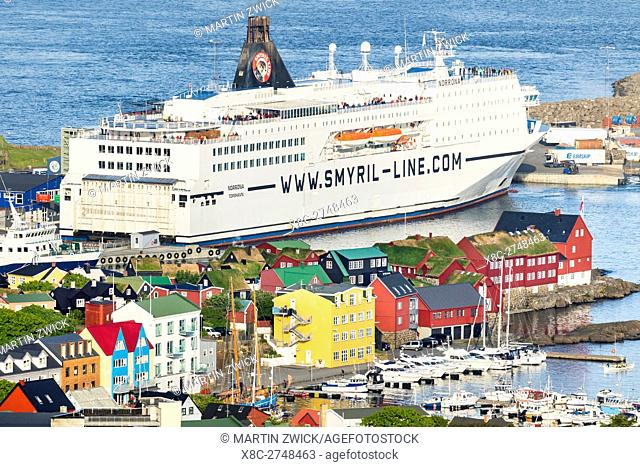 The ferry to Iceland, peninsula Tinganes with the red houses of the government in the foreground. Torshavn (Thorshavn) the capital of the Faroe Islands on the...