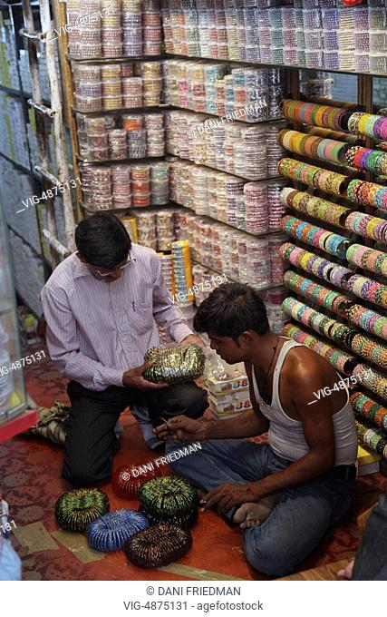 Man buying colourful glass bangles for his wife in the bangle market at Balli Maran in Old Delhi, Delhi, India. - OLD DELHI, DELHI, India, 11/07/2014