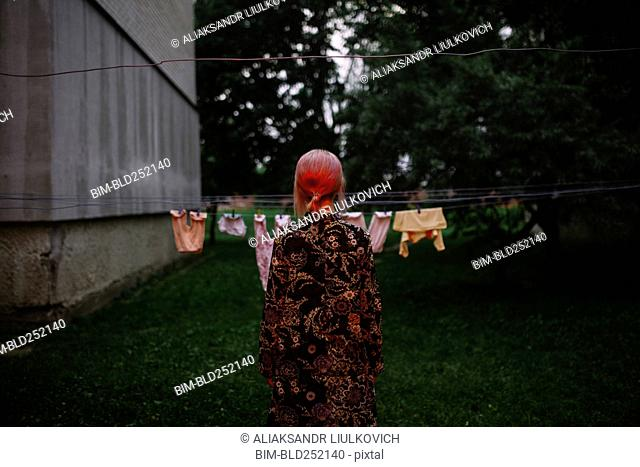 Caucasian woman staring at clothesline