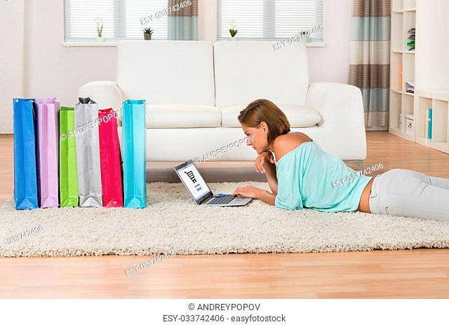Young Woman Shopping Online On Laptop While Lying On Carpet At Home