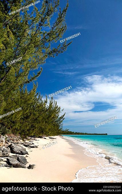 A woman walking along a beach near the Orange Creek area of Cat Island, Bahamas