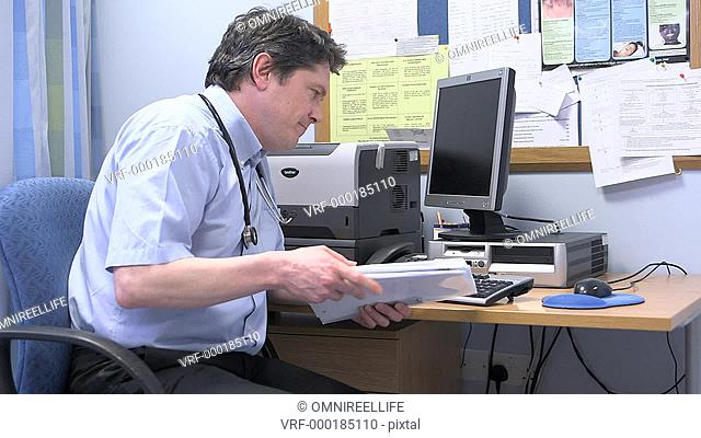 WS Tired male doctor looking at documents in his office