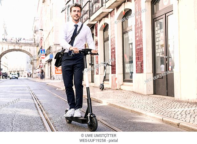 Young businessman riding e-scooter in the city, Lisbon, Portugal