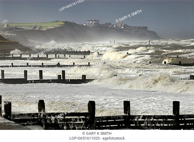 England, Norfolk, Mundesley. Large waves breaking over groynes on the beach near the coastal village of Mundesley