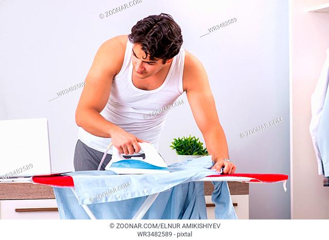 Young man freelancer ironing in the bedroom