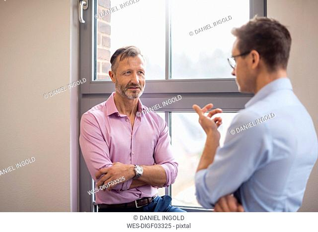 Two businessmen talking at the window