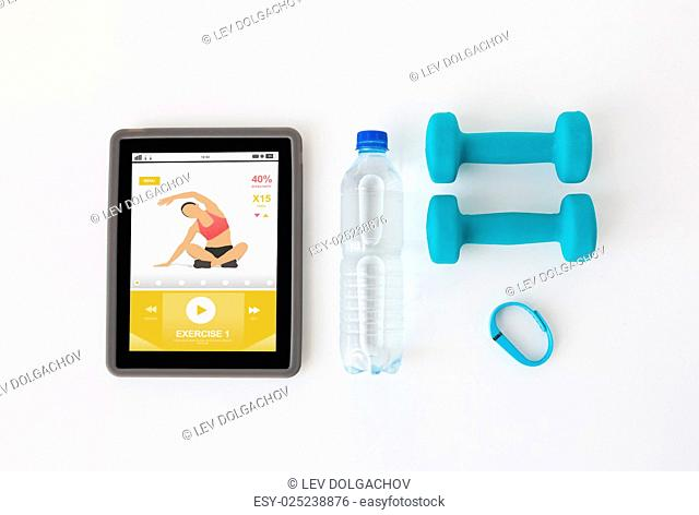 sport, healthy lifestyle, fitness and technology concept - close up of tablet pc computer with dumbbells, fitness tracker and water bottle over white background