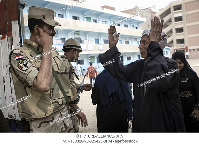 dpatop - An Egyptian man speaks with an army officer after voting on the 3rd day of the 2018 Egyptian presidential elections, at a polling station in Monufia