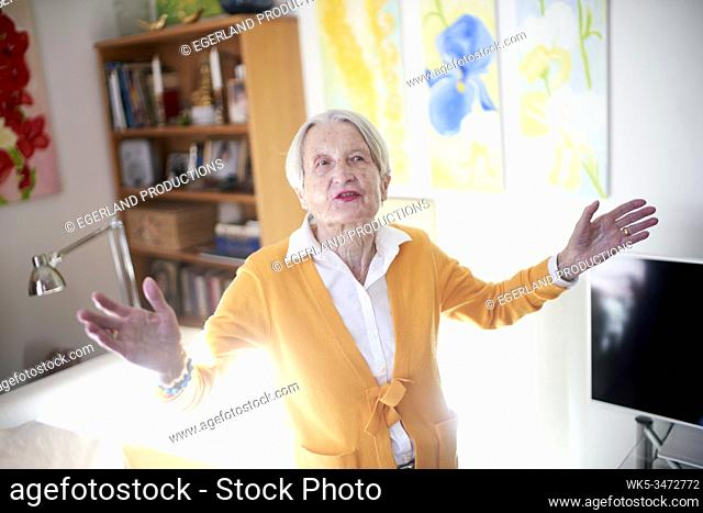 Senior woman at home with arms open