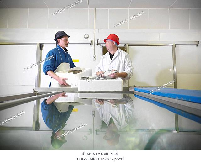 Workers holding fresh fish in plant