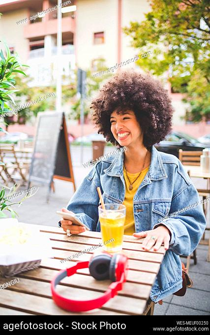 Happy young woman with afro hairdo at an outdoor cafe in the city