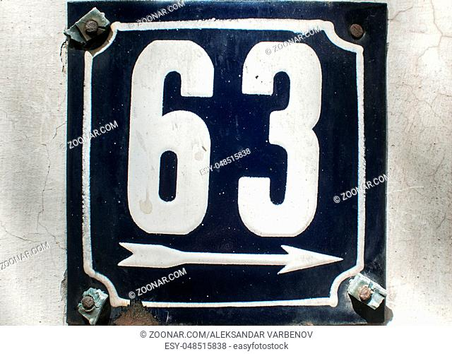 Weathered grunge square metal enameled plate of number of street address with number 63 closeup