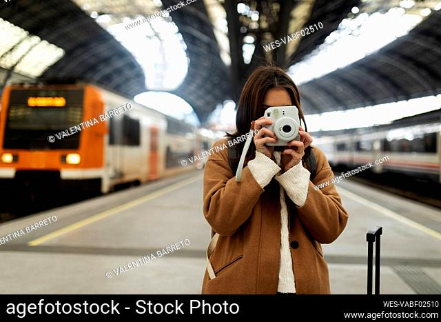 Young woman taking picture with camera at the train station