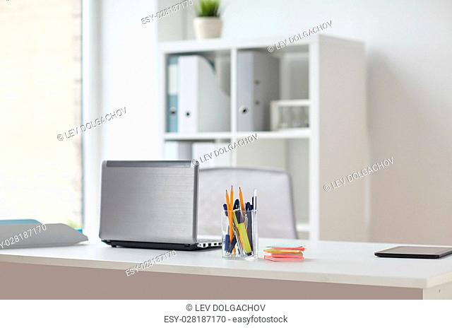 business and interior concept - laptop with pen and stickers on office table