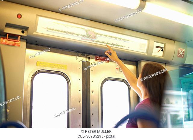 Woman pointing to station map in train carriage