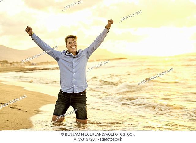 Young man kneeling on beach, wearing business shirt, in holiday destination Malia, Crete, Greece