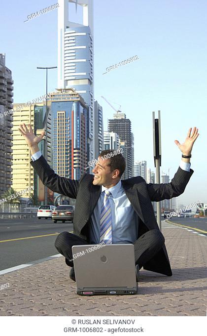 Jubilating businessman with laptop on Shaikh Zayed Road in Dubai