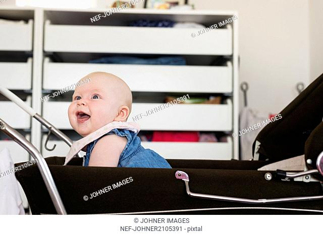 Smiling little girl in baby carriage