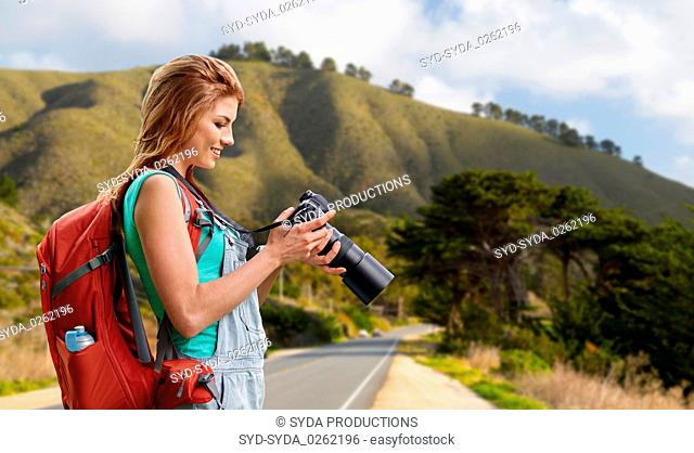 woman with backpack and camera at big sur hills