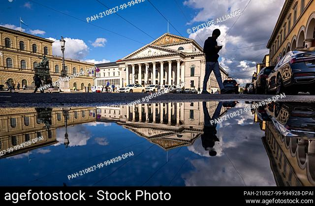 27 August 2021, Bavaria, Munich: The Bavarian State Opera is reflected in a puddle on Maximilianstrasse in the evening. On the left is the equestrian monument...