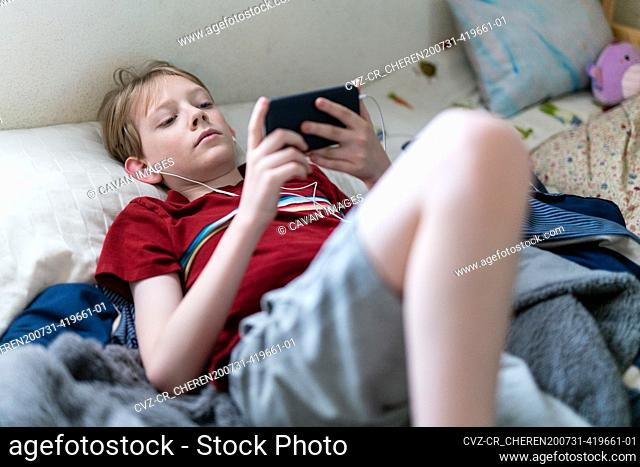 Young boy lying on bed looking at smartphone with earbuds in ears
