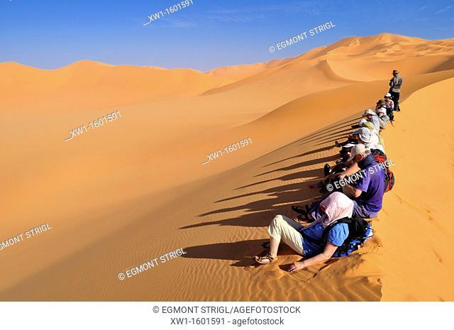 group of tourists sitting on a sanddune of Erg Mehedjibat, Adrar n' Ahnet, Algeria, Sahara, North Africa