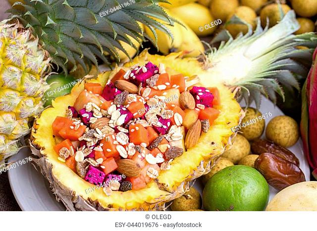 Fresh tropical fruit salad in pineapple with oat flakes, raisins, nuts, sesame and mix sliced fruits ( dragon fruit, pineapple, banana, mango