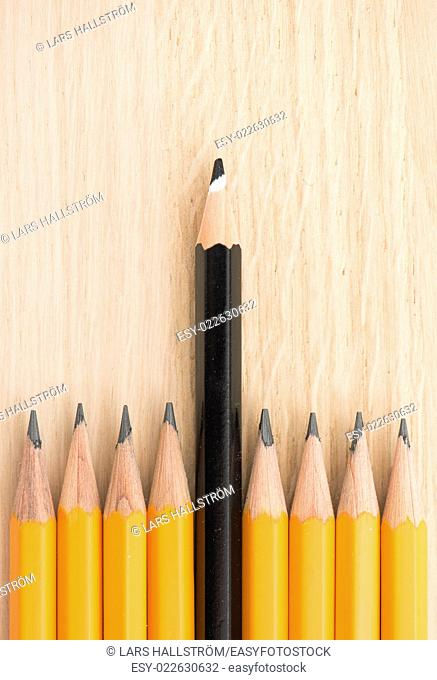 Pencils on office table, one is in front of the others. Concept of leadership, success at work and management