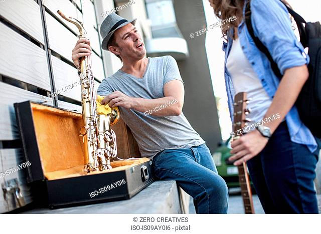 Street musician cleaning saxophone