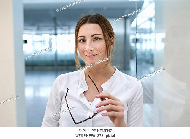 Portrait of confident young businesswoman holding glasses