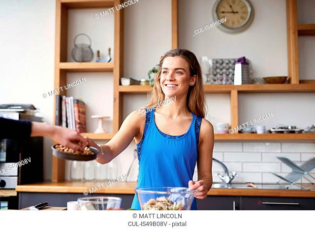 Young woman at kitchen table offering nuts to friend