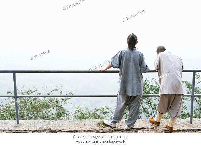 Shaolin nuns stand and perch at a railing at the statue of Bodhidharma at the Shaolin Temple
