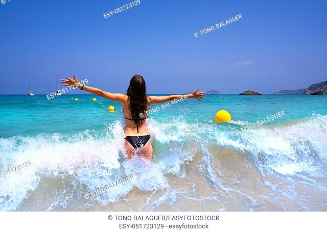 Ibiza beach girl splashing water open arms in Balearic islands