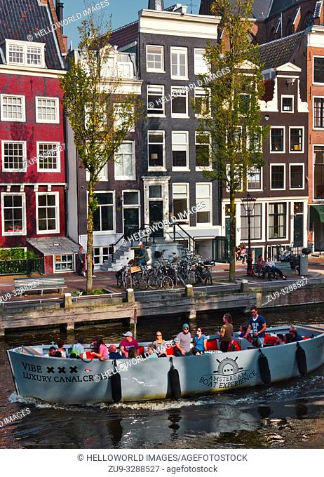 Tourists on a luxury canal cruise and traditional canal houses, Amsterdam, Netherlands, Europe