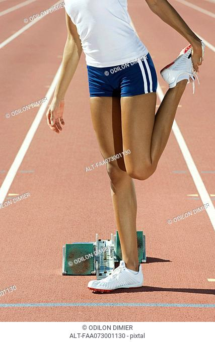 Female runner stretching, cropped